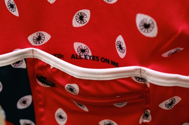 Detail of red women's cycling jersey with repeated eye print pattern