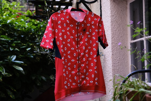 Red women's road cycling jersey hanging up outside