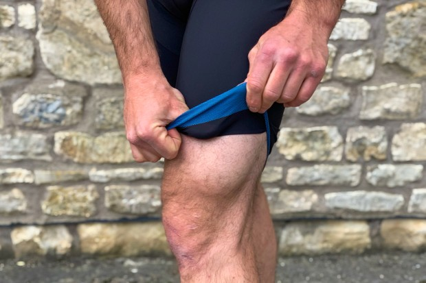 Man wears 7Mesh MK3 padded cycling short, revealing silicone gripper at the base of the shorts' hem