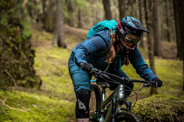 Woman riding a mountain bike in the forest wearing the MET Parachute MCR helmet