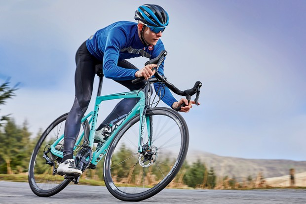 Male cyclist riding teal road e-bike