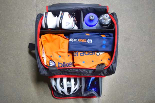 A Black Line Sprinting bag for cycling kit including a helmet, shoes, clothes, water bottles and glasses with individual compartments