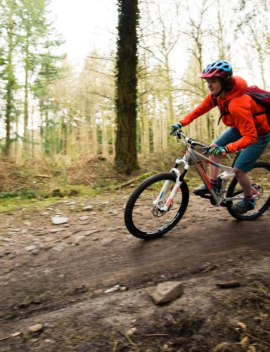 female cyclist riding mountain bike in woods