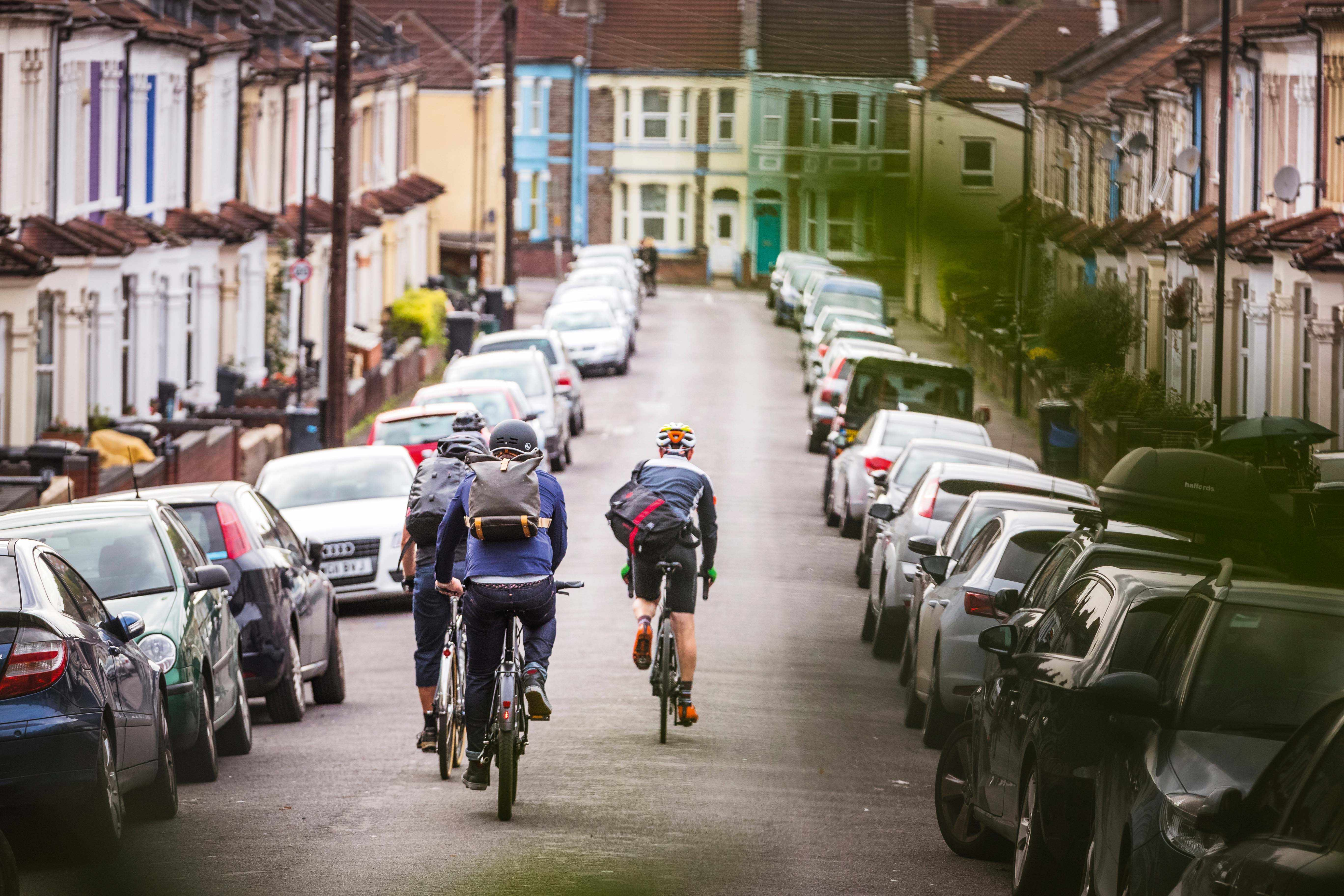 Four commuters cycling along residential street