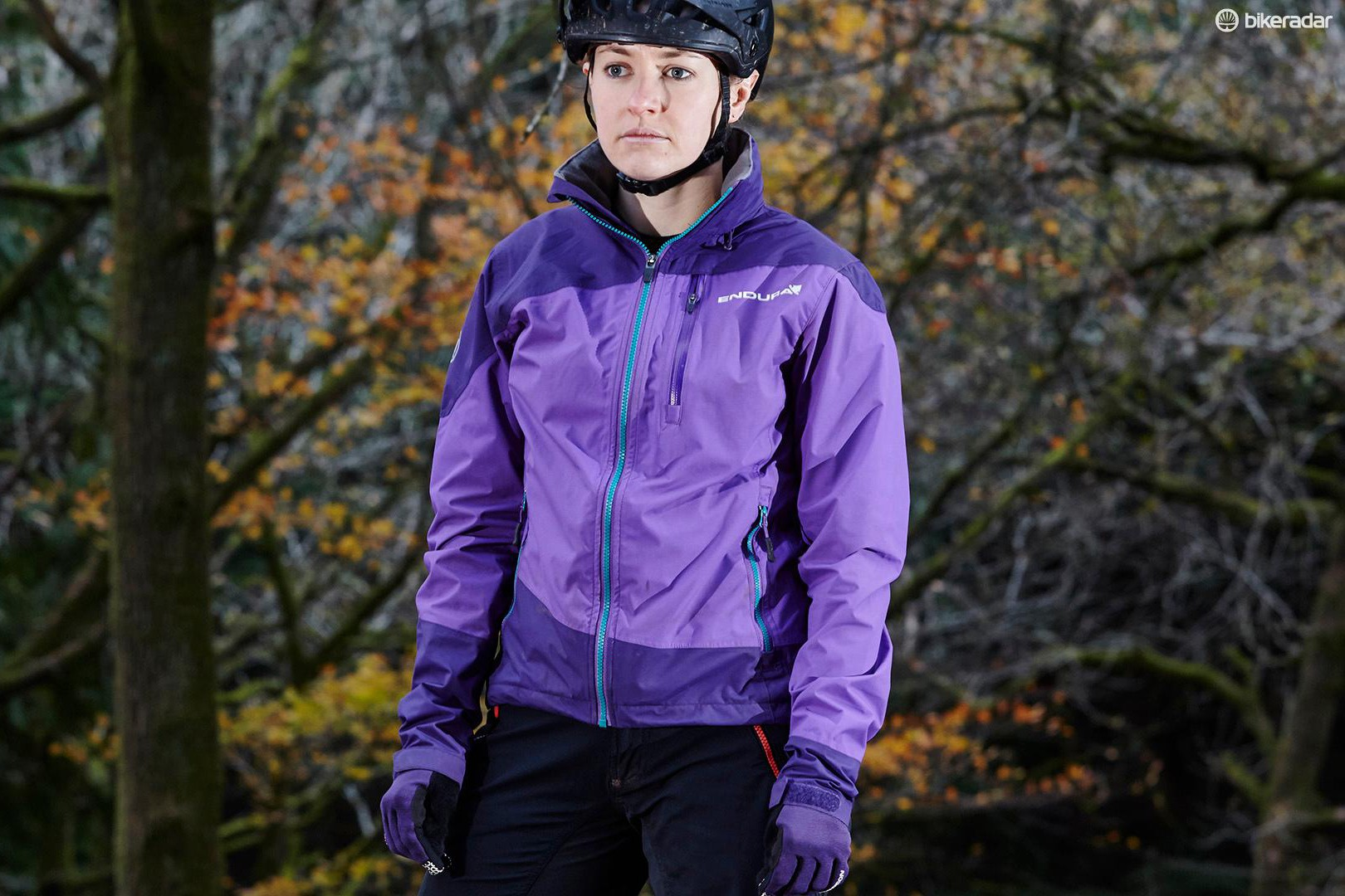 female cyclist wearing purple mountain bike jacket