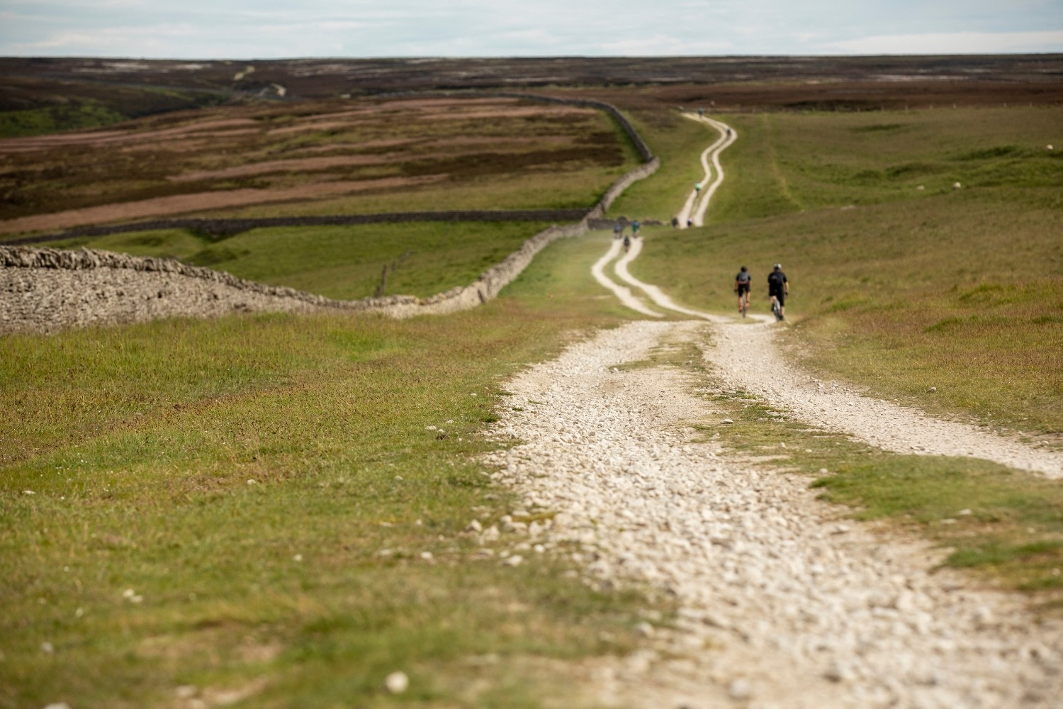 This picture shows two cyclists riding along a long gravel path in the countryside