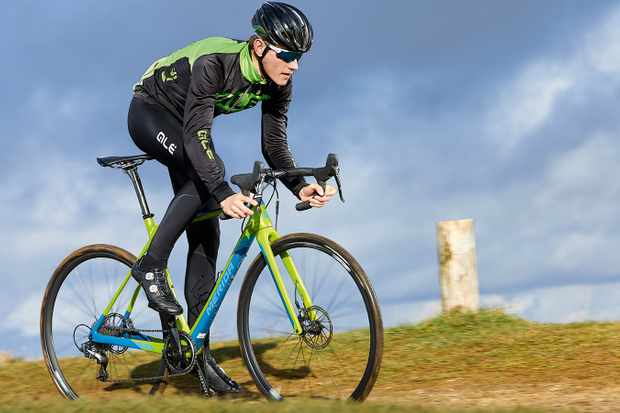 Male cyclist riding green and blue road bike in countryside