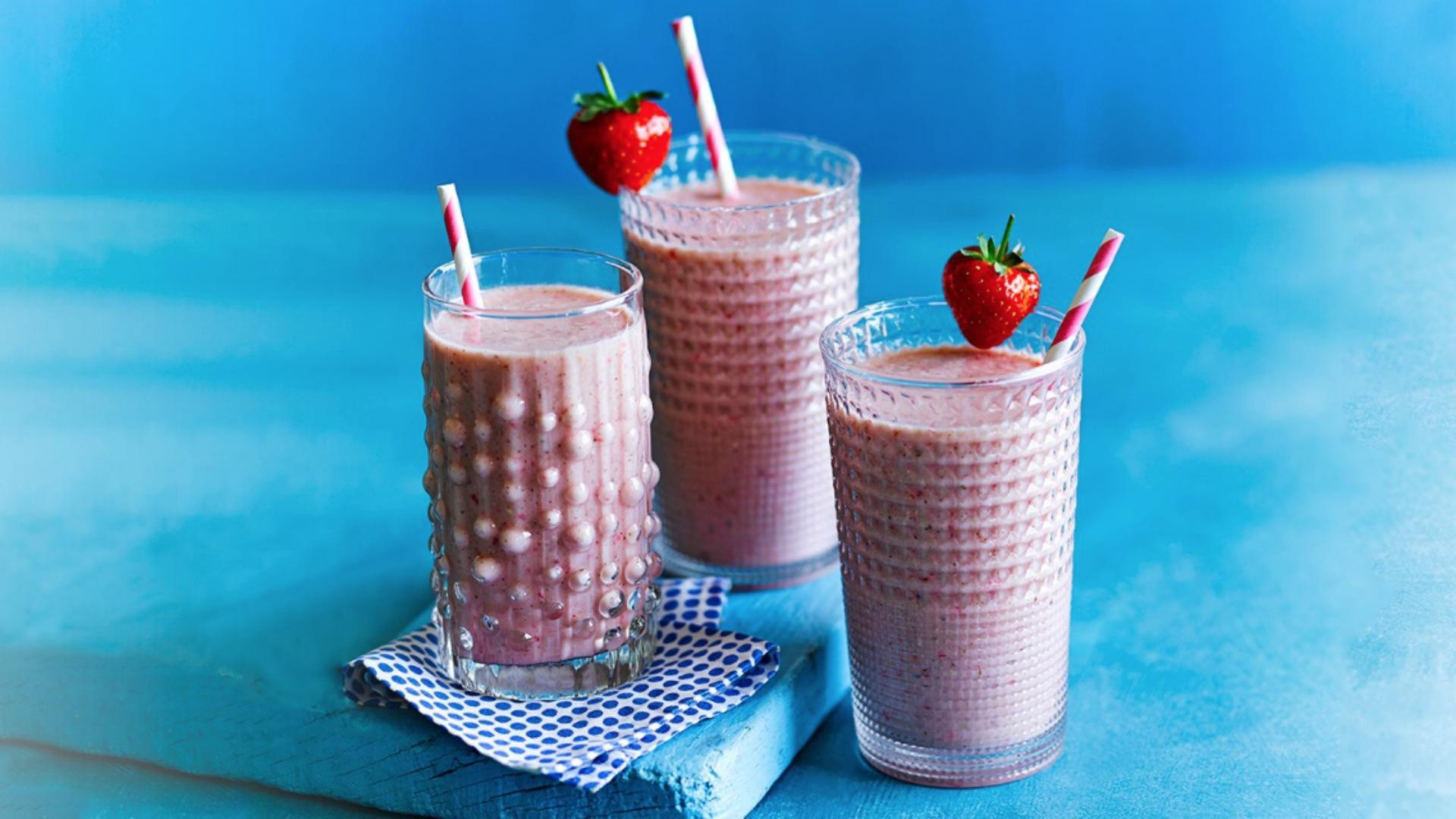 three pink smoothies with straws