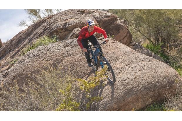Man rides Pivot electric mountain bike riding down a large rock