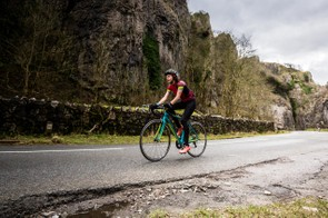 female cyclist riding blue road bike chedder gorge