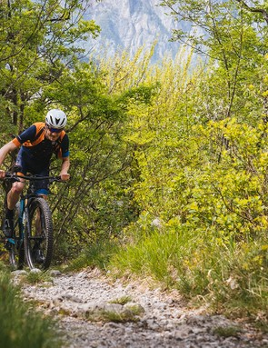 male cyclist riding blue full suspension mountain bike