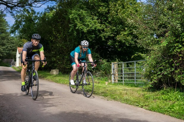 Two road cyclists riding along a country lane