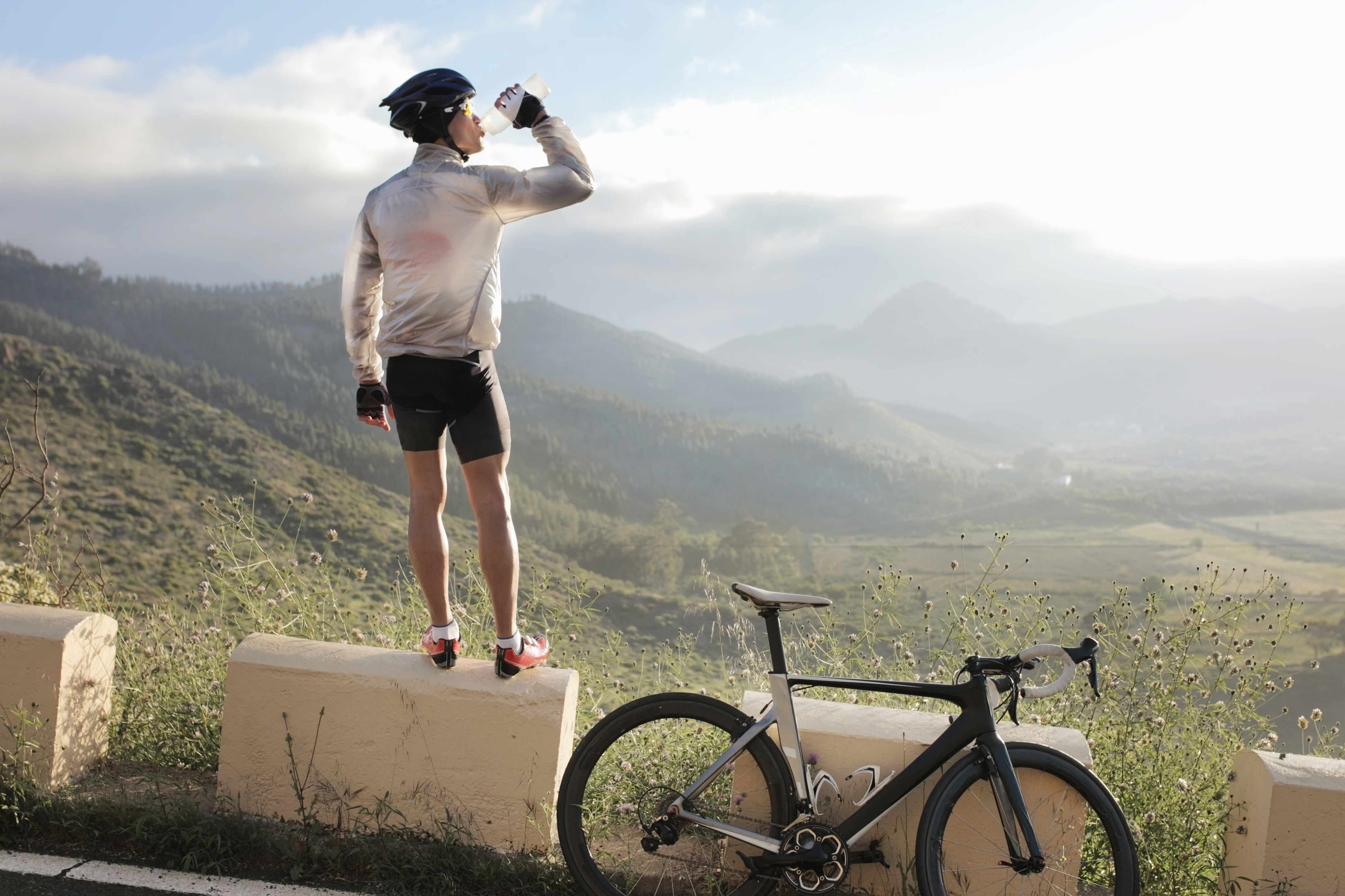 male cyclist standing on stone looking over countryside