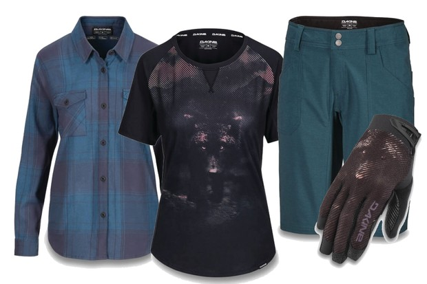 A selection of women's mountain bike clothing from Dakine with a blue shirt, black T-shirt, dark green shorts and black gloves