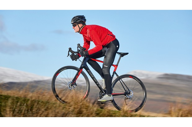 Male cyclist riding red and black bike in countryside