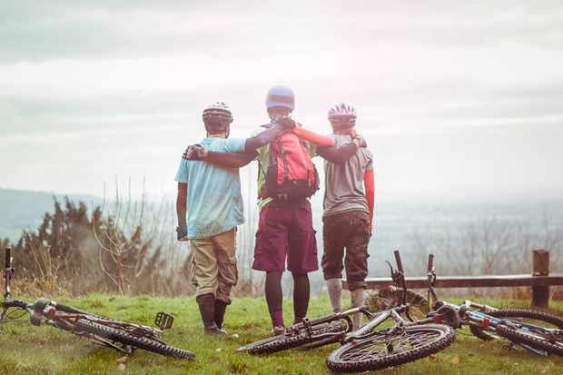 three cyclists looking over countryside