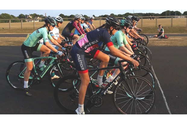 A group of women on bikes lined up to start a road cycling race