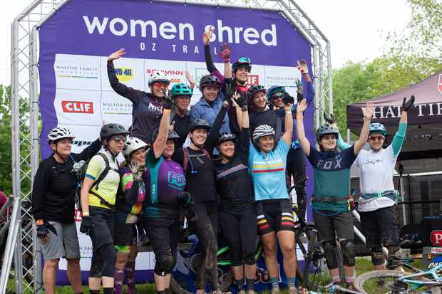 Group of happy looking women mountain bikers on a stage with a banner that says Women Shred