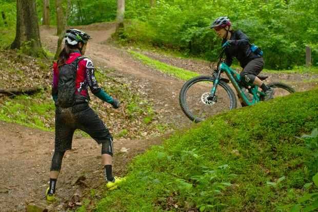One woman mountain biker riding a trail while another woman provides coaching