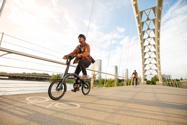 Ariv Merge folding electric bike being ridden over a bridge in the sunshine