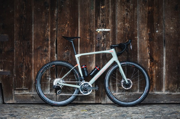 Grey road bike against a wooden fence