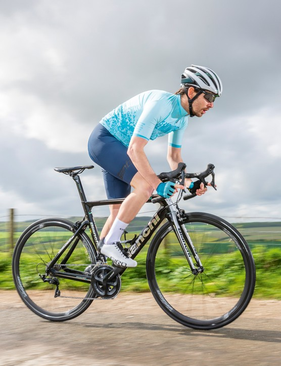 male cyclist riding black road bike in countryside