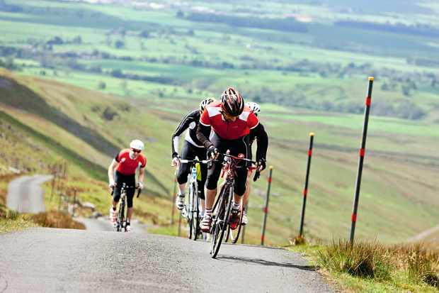 Men cycling up a steep hill on road bikes