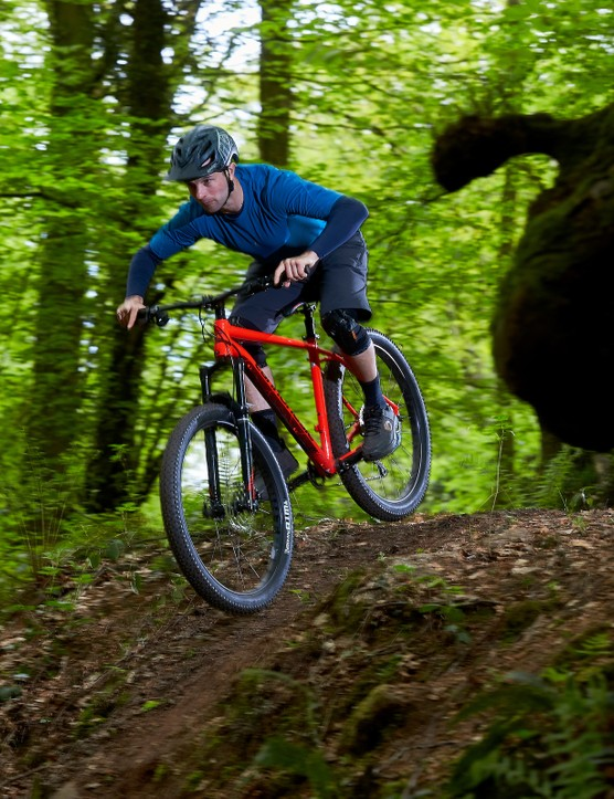 male cyclist riding red orange hardtail mountain bike in woods