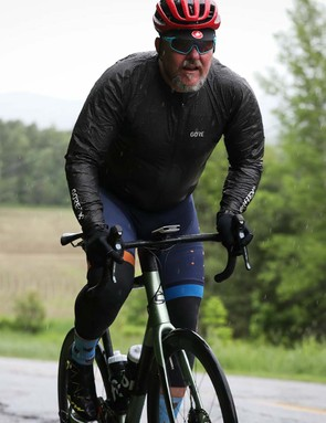 male cyclist riding green road bike in countryside