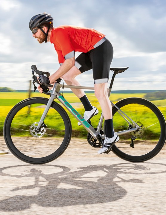 male cyclist riding grey road bike in countryside