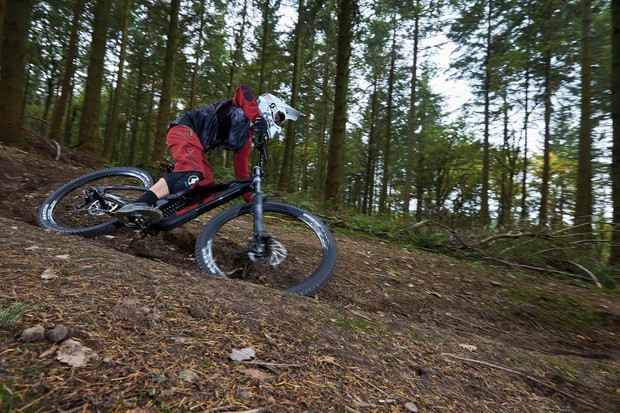 Cyclist riding black full suspension mountain bike in woods forest
