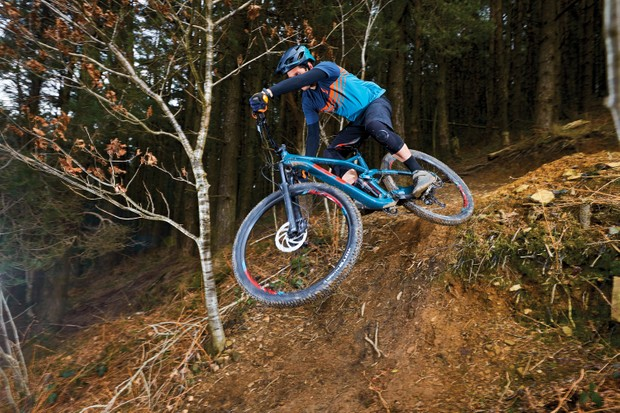 Male cyclist riding blue full-suspension mountain bike in woods