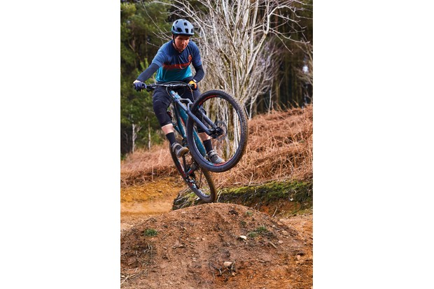 Male cyclist riding blue full suspension mountain bike in woods