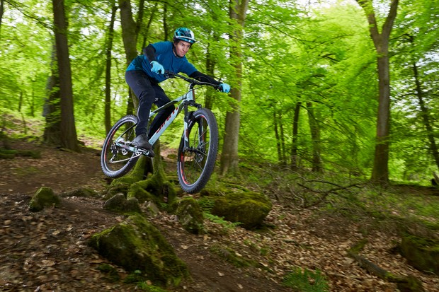 male cyclist riding light blue hardtail mountain bike in forest of dean