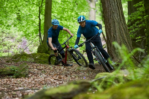 two male cyclists riding mountain bikes through the forest of dean
