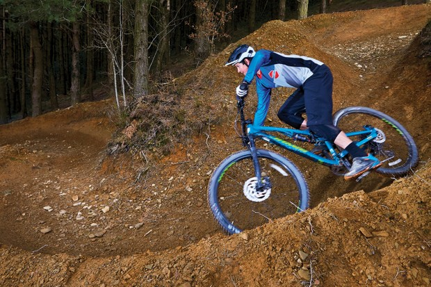 Male cyclist riding blue full suspension mountain bike down hill