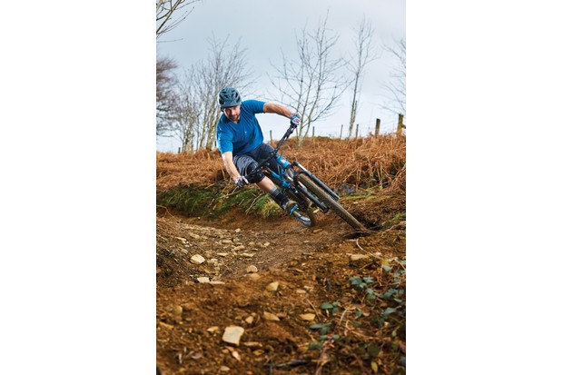 Cyclist riding blue mountain bike woods