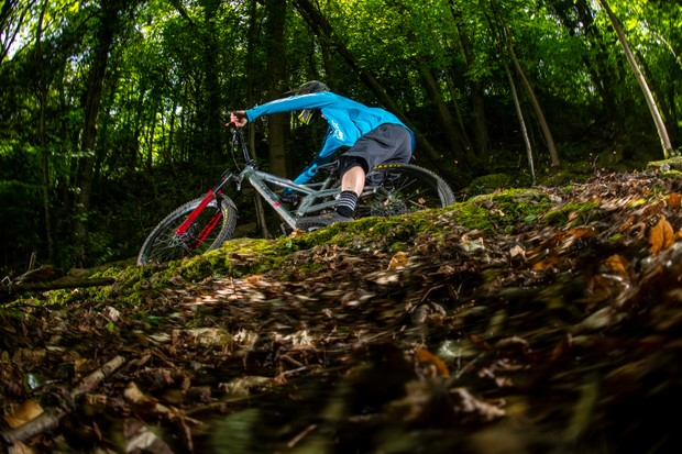 BikeRadar Technical Editor Alex Evans rides his long-term Orange Stage 6 RS enduro mountain bike around a bermed corner in the forest