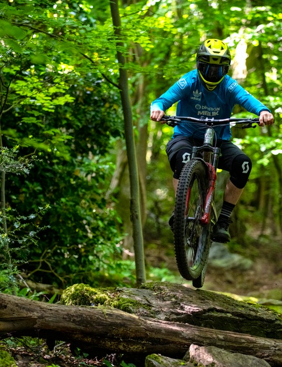 BikeRadar Technical Editor Alex Evans rides his long-term Orange Stage 6 RS enduro mountain bike over a rock in the forest