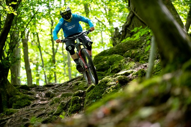 BikeRadar Technical Editor Alex Evans rides his long-term Orange Stage 6 RS enduro mountain bike over some roots in the forest
