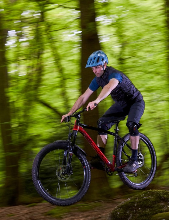 Male cyclist riding black and red hardtail mountain bike in forest of dean