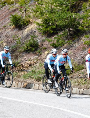 group of road cyclist riding down hill