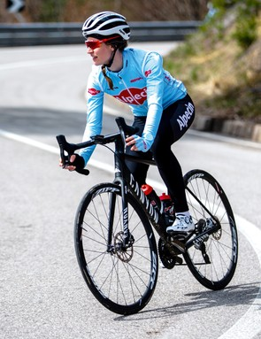 female cyclist riding road bike round bend and down hill