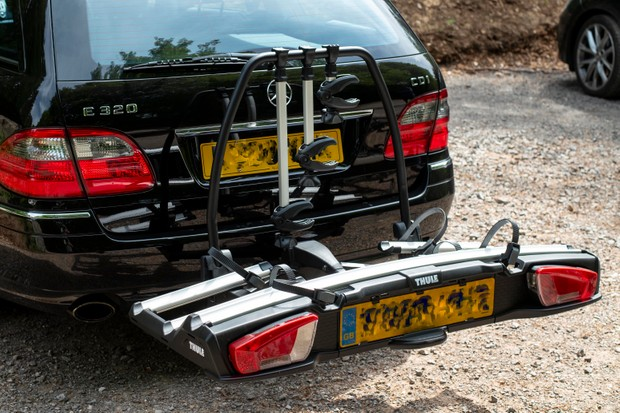 Thule VeloSpace XT 3 towbar mounted bike rack attached to a black Mercedes estate car with no bikes on it
