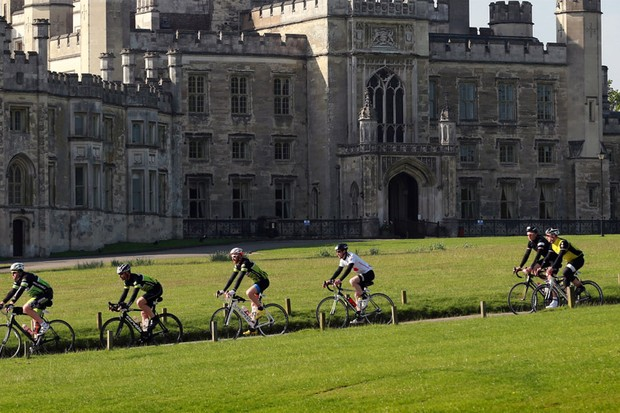 Cyclists riding past a castle during a stage of L'Etape UK