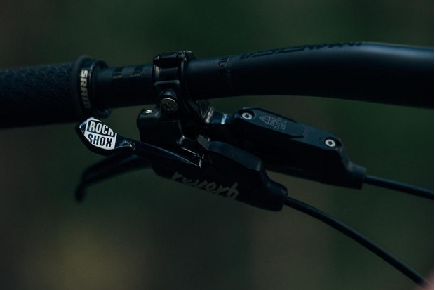 Detail photograph of the controls of the RockShox Reverb Stealth dropper post mounted on a bicycle handlebar