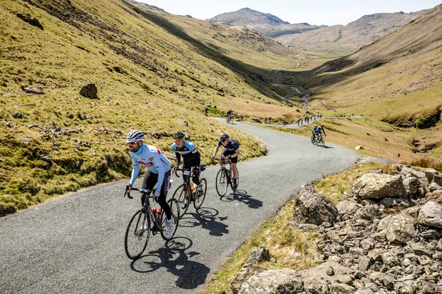 team alpecian cyclist riding in mountains