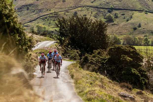 4 cyclists from team alpecin riding road bike in mountains