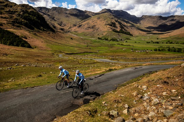 Two cyclists from Team Alpecin riding road bikes in mountains