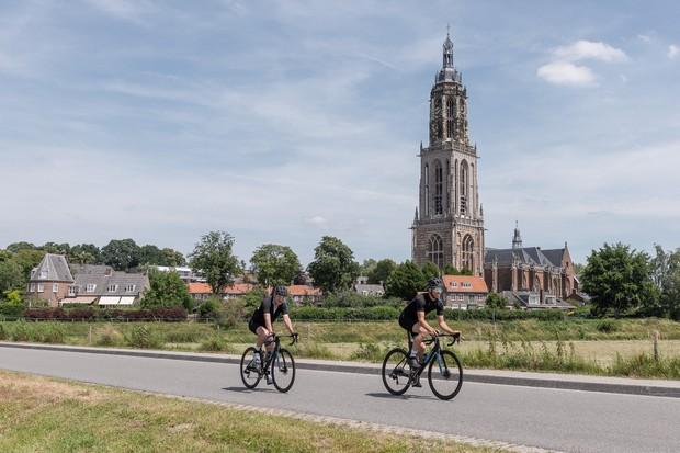 Two male cyclist riding road bike past church